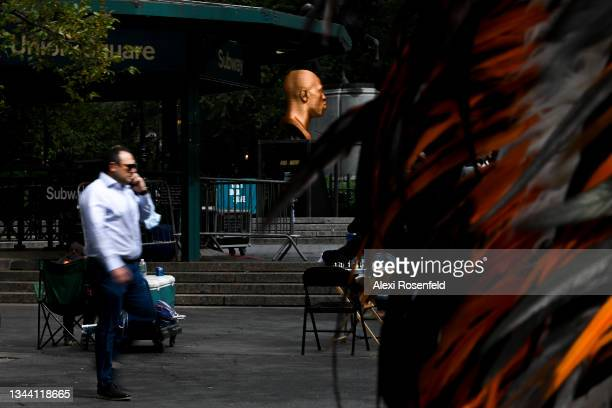 """Person walks past Confront Art's First Exhibition SEEINJUSTICE sculpture """"FLOYD"""" in Union Square on September 30, 2021 in New York City...."""
