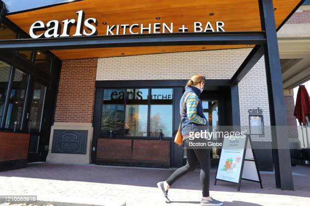Person walks past Earls Kitchen + Bar in Somerville, MA on April 19, 2020. It is one of the Somerville restaurants now allowed to sell groceries...