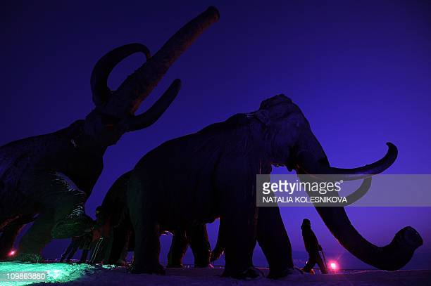 A person walks past giant bronze sculptures of mammoths on March 7 2011 during the World Biathlon Championships in the Siberian city of...