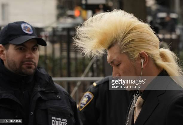 A person walks past New York State Court officers right before Harvey Weinstein arrives at Manhattan Supreme Court February 20 2020 for the third day...