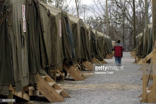 A person walks past tent houses in The Village a makeshift city of tents where about 100 families are awaiting FEMA trailers on December 2 2005 in...