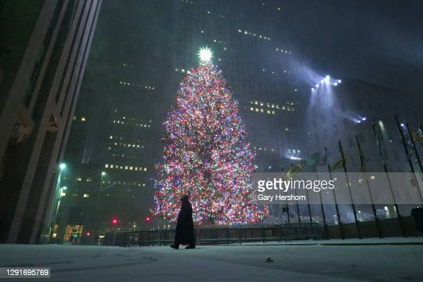 Person walks past the Christmas tree in Rockefeller Center during a snowstorm on December 16, 2020 in New York City.