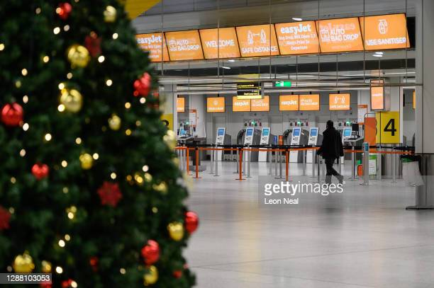 Person walks past the Christmas tree in the near-empty North Terminal at Gatwick Airport on November 27, 2020 in London, England. The airport will...
