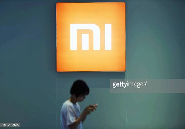 Person walks past the logo of Xiaomi while looking at a smartphone in Hangzhou in China's eastern Zhejiang province on July 9, 2018. - Chinese...