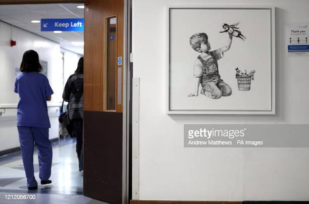 Person walks past the new artwork painted by Banksy during lockdown, entitled 'Game Changer', which has gone on display to staff and patients on...