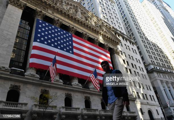 Person walks past the New York Stock Exchange at Wall Street on November 16, 2020 in New York City. - Wall Street stocks rose early following upbeat...