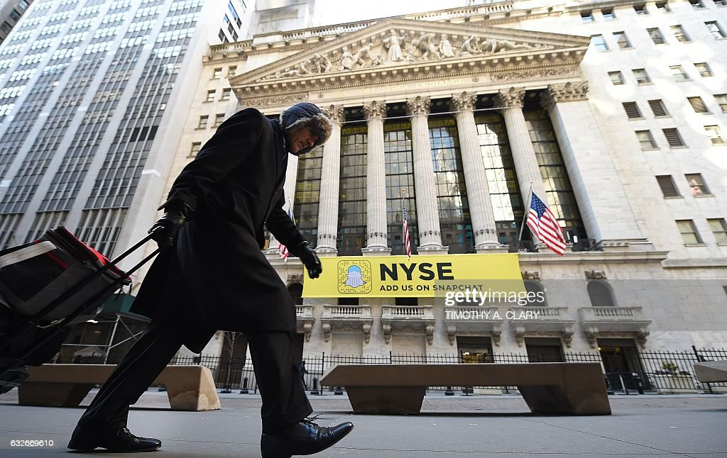 A person walks past the New York Stock Exchange on Wall Street in New York January 25, 2017. The Dow Jones Industrial Average, the most famous equity index benchmark on Wall Street shot above 20,000 for the first time at the open Wednesday. / AFP / TIMOTHY