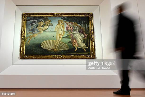 A person walks past the 'The Birth of Venus' painted in 1485 by Italian painter Sandro Botticelli during a press preview for the reopening the rooms...