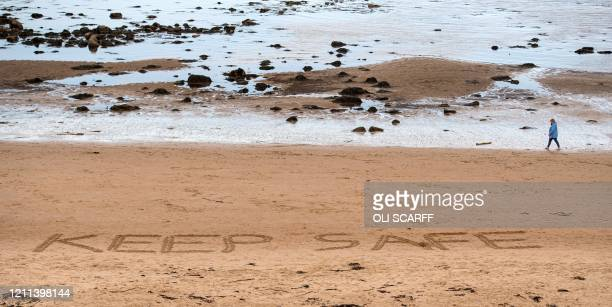 "Person walks past the words ""Stay Safe"", etched into the sand on the beach in Whitley Bay, north east England on April 30 as life in Britain..."