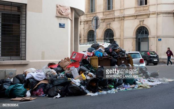 A person walks past uncollected trash during a strike by refuse collectors on October 18 in Marseille southern France / AFP PHOTO / BERTRAND LANGLOIS