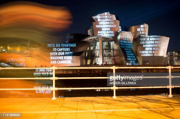 A person walks past US artist Jenny Holzer's projection mapping creation entitled For Bilbao and projected on the Guggenheim Bilbao Museum's facade...