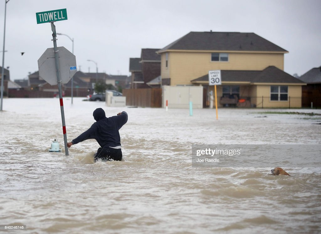 A person walks through a flooded street with a dog after the area was inundated with flooding from Hurricane Harvey on August 28, 2017 in Houston, Texas. Harvey, which made landfall north of Corpus Christi late Friday evening, is expected to dump upwards to 40 inches of rain in Texas over the next couple of days.