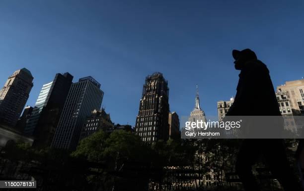 A person walks through Bryant Park in front of the Empire State Building as the sun rises on May 18 2019 in New York City
