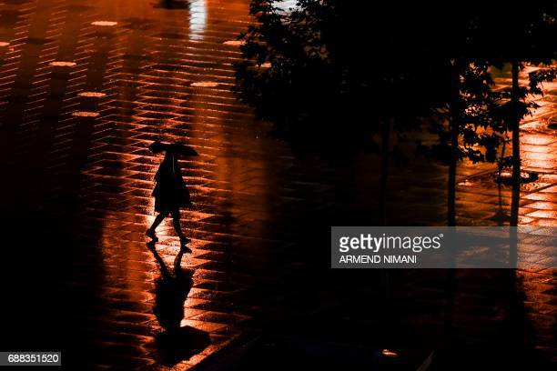 A person walks through Mother Teresa square in Pristina during a heavy rainfall on May 25 2017 / AFP PHOTO / Armend NIMANI