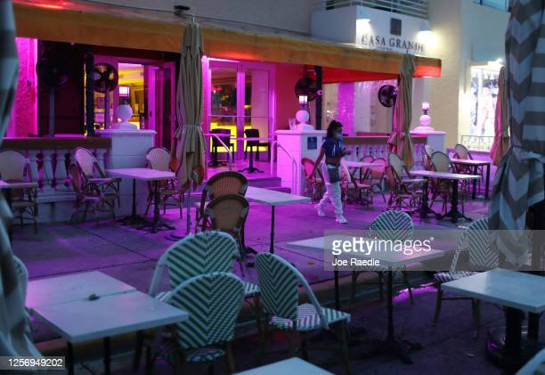 Person walks through the closed outdoor seating area of a restaurant as a curfew from 8pm to 6am is put in place on July 18, 2020 in Miami Beach,...
