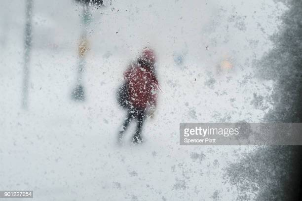 A person walks through the streets of Boston as snow falls from a massive winter storm on January 4 2018 in Boston Massachusetts Schools and...
