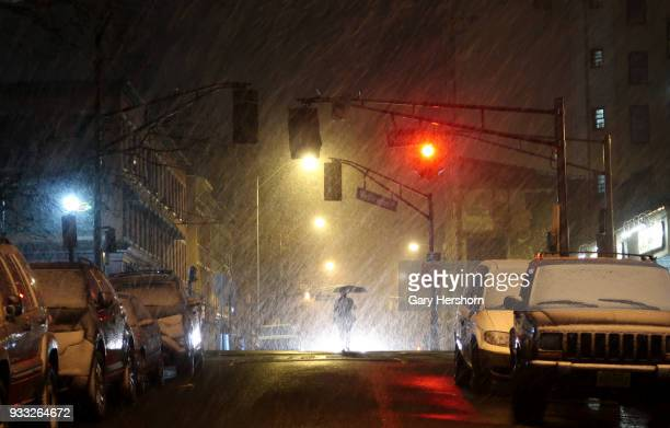 A person walks to the subway in a predawn snowstorm on March 13 2018 in Hoboken New Jersey