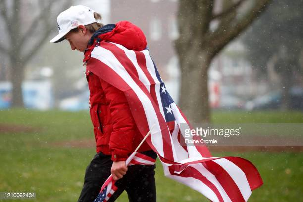 Person walks towards the Capitol building along with others to express their unhappiness with Governor Gretchen Whitmer's Stay Safe, Stay Home...