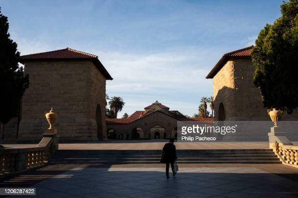 Person walks towards the main quad during a quiet morning at Stanford University on March 9, 2020 in Stanford, California. Stanford University...