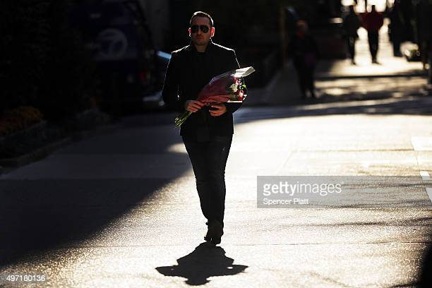 A person walks with flowers to place in front of the Consulate General of France in New York the day after an attack on civilians in Paris on...