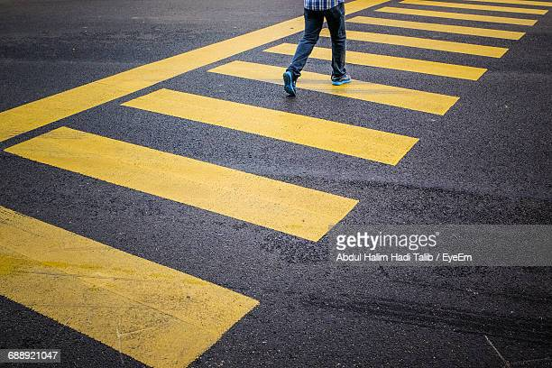 person walling on zebra crossing - pedestrians stock photos and pictures