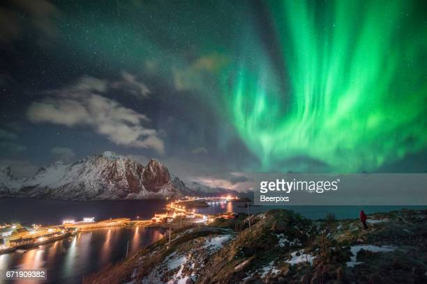 Person was looking with beautiful dancing aurora borealis over Hamnoy and Reine, Lofoten, Norway