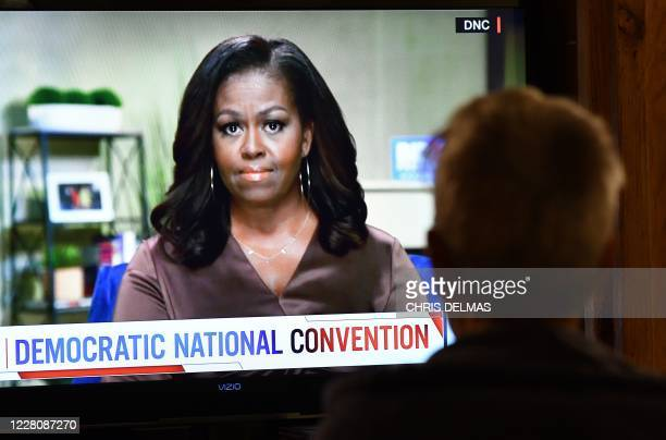 Person watches former First Lady Michelle Obama speak during the opening night of the Democratic National Convention, being held virtually amid the...