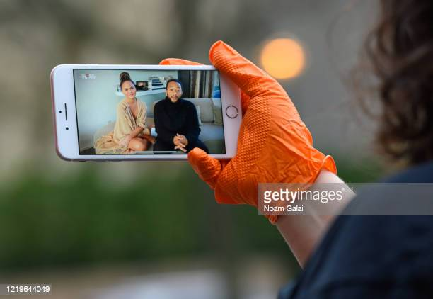 A person watches 'One World Together at Home' by Global Citizen on her phone in Kips Bay during the coronavirus pandemic on April 18 2020 in New York...