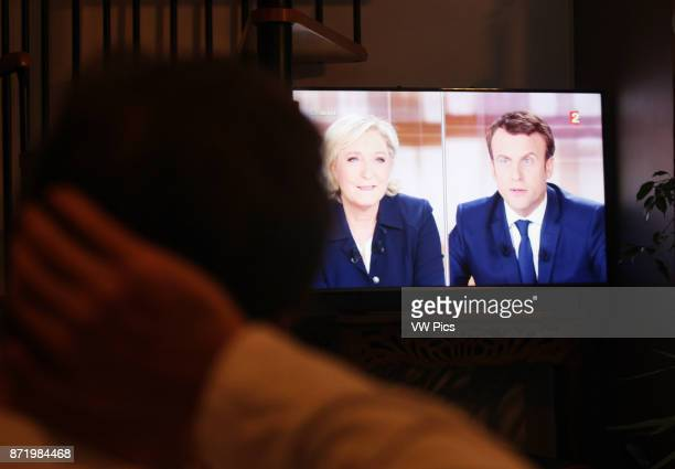 Person watches the French presidential election candidate for the En-Marche movement Emmanuel Macron and Marine Le Pen, National Front Party during...