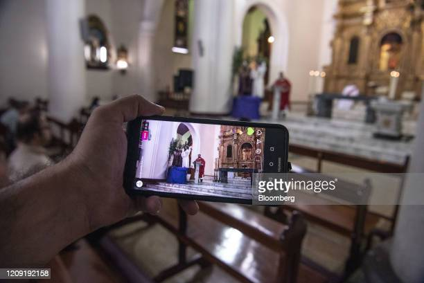 A person watches the live broadcast of a Palm Sunday mass in Caracas Venezuela on Sunday April 5 2020 Amid the coronavirus as the world's major...