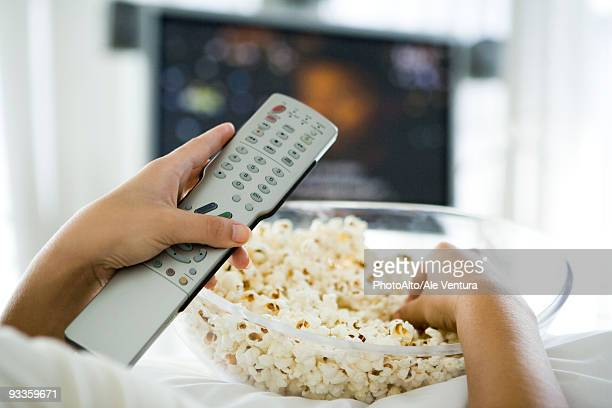 Person watching television, holding remote control and bowl of popcorn, cropped view