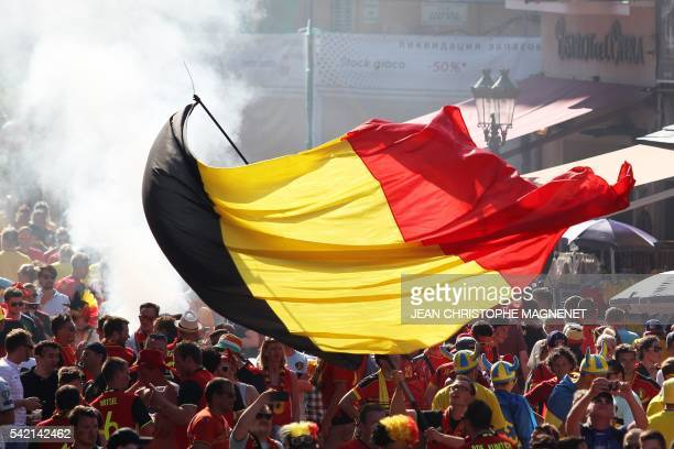 Person waves a Belgian flag as Belgium's and Sweden's supporters cheer prior to the Euro 2016 football match between Sweden and Belgium in Nice,...