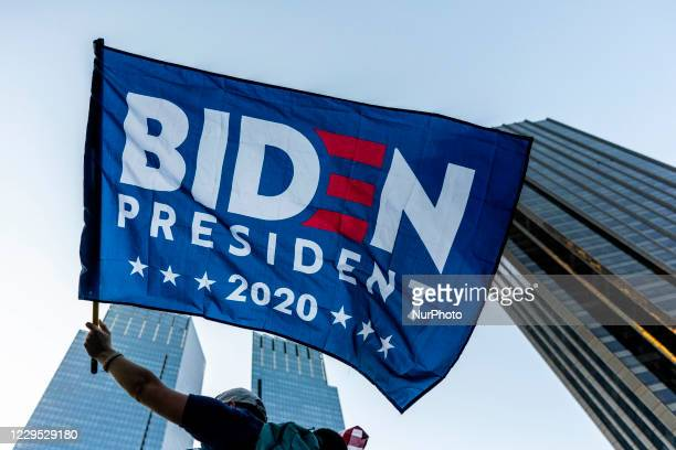 Person waves a Biden President flag outside of the Trump International Hotel & Tower at Columbus Circle on Saturday, Nov. 2020 in New York, NY....