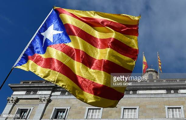 A person waves a Catalan proindependence 'Estelada' flag as the Spanish flag and the Catalan official 'Senyera' flag are seen on top of the...