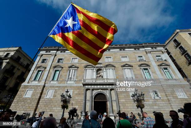 A person waves a Catalan proindependence flag in front of the 'Generalitat' palace in Barcelona on October 30 2017 Spain enters uncharted and...