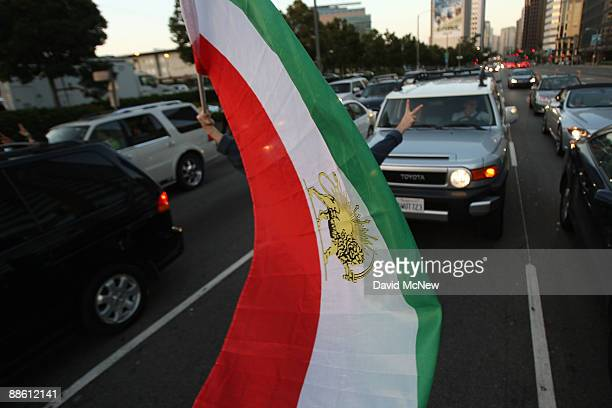A person waves a flag as IranianAmericans and supporters protest what they say are crimes against humanity and democracy committed by the government...