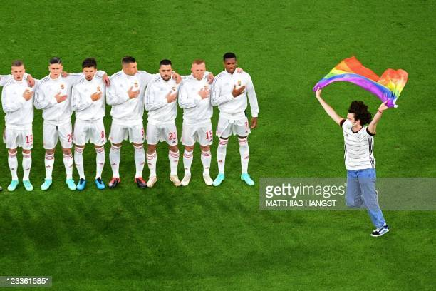 Person waving the rainbow flag runs on the pitch as the Hungary players line up for the national anthems the UEFA EURO 2020 Group F football match...