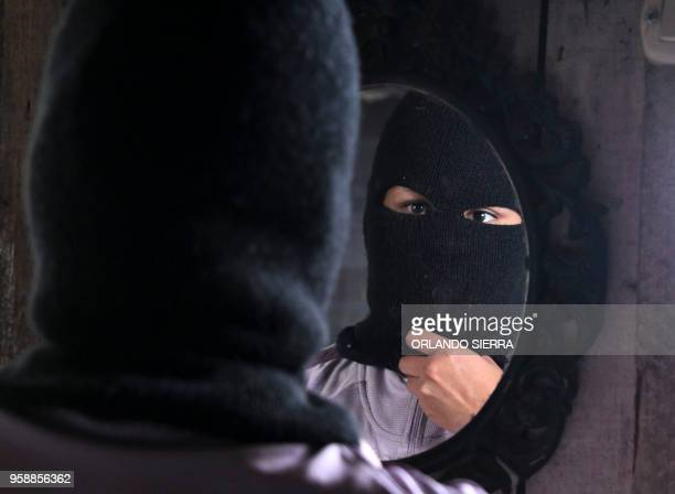 A person wearing a balaclava offers an interview to AFP in the poor neighbourhood of Nueva Capital on the outskirts of Tegucigalpa on May 13 2018...
