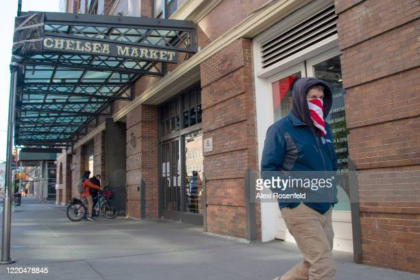 A person wearing a bandana a as a mask walks past Chelsea Market amid the coronavirus pandemic on April 22 2020 in New York City United States...