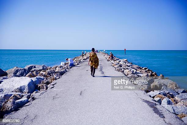 Person wearing a black hat walking on a concrete jetty December 3 2016 in Venice Florida