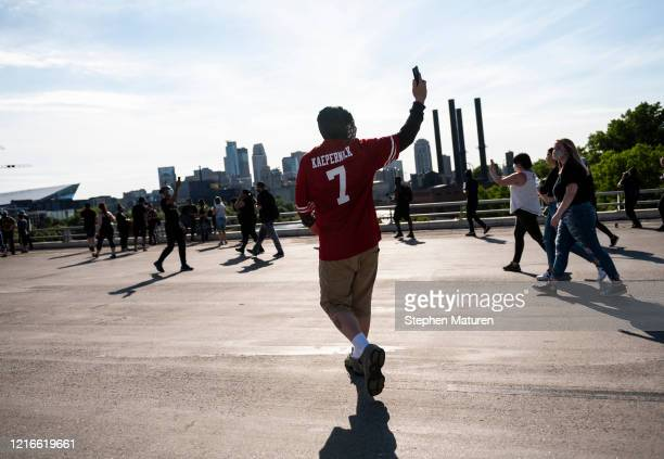 Person wearing a Colin Kaepernick jersey walks with a crowd marching to protest the death of George Floyd on the I-35W bridge over the Mississippi...