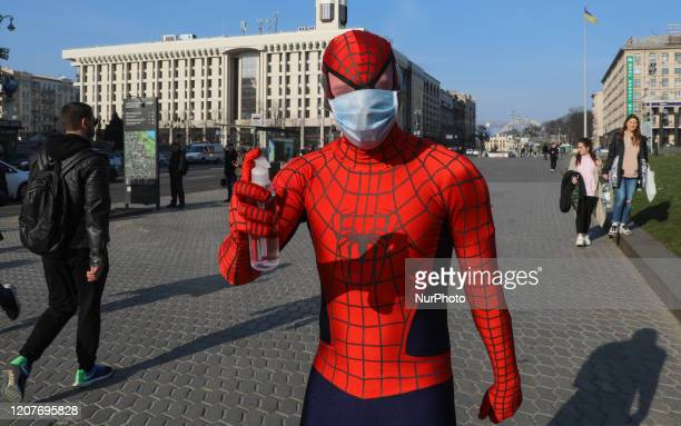 A person wearing a costume of a SpiderMan with a disposable face mask propose a handsanitizer to passersby in Kyiv Ukraine March 19 2020 26 cases of...