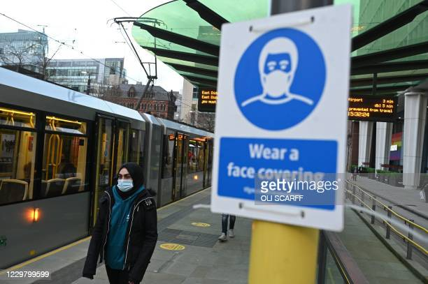 Person wearing a face covering due to the COVID-19 pandemic, waits to board a tram in Manchester, northwest England, on November 26, 2020. - London...