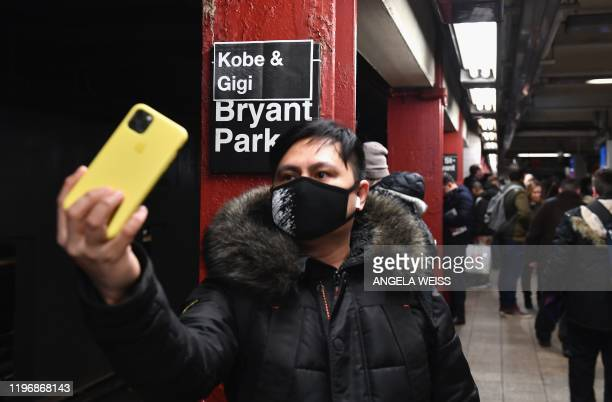 A person wearing a face mask takes a selfie of a makeshift sign reading Kobe Gigi Bryant Park at the Bryant Park subway station on January 27 2020 in...
