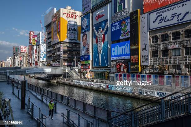 Person wearing a face mask walks alongside the canal in Dotonbori, one of Osaka's most popular tourist areas, on May 13, 2020 in Osaka, Japan....