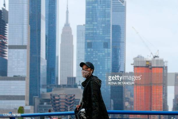 Person wearing a face mask walks in Weehawken, New Jersey, on November 11 with the New York skyline in the background. - Mayor Bill de Blasio said...