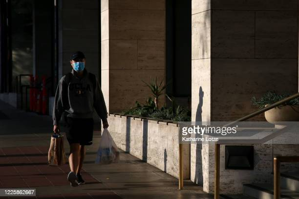 A person wearing a face mask walks on May 10 2020 in Westwood California The United States has more than 15 million reported cases and more than...
