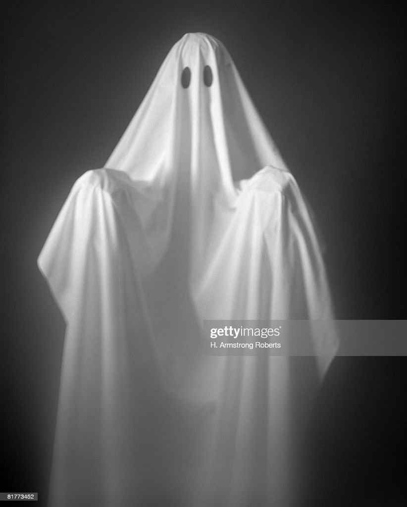 Person Wearing A Ghost Costume, Made Out Of A White Sheet With Two Holes In It. Highlights Are On The Sheet, The Background Is Pitch Black. : Stock Photo