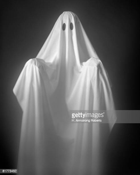 Person Wearing A Ghost Costume, Made Out Of A White Sheet With Two Holes In It. Highlights Are On The Sheet, The Background Is Pitch Black.
