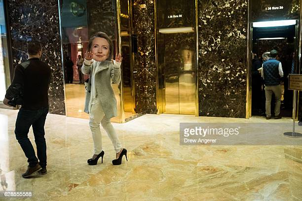 A person wearing a Hillary Clinton mask walks through the lobby at Trump Tower December 8 2016 in New York City Presidentelect Donald Trump and his...
